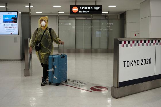 지난 4월 일본 나리타 국제공항에 한 여행각이 고글과 방호복을 착용한 채 입국장에 들어서고 있다. [AP=연합뉴스]