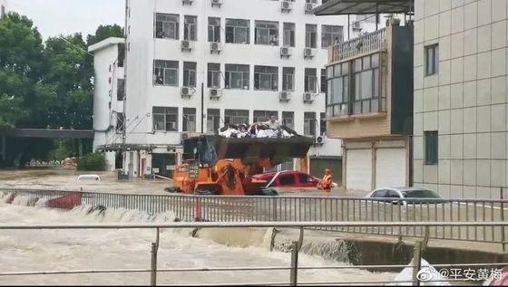 중국 후베이성 황메이현의 화닝고교 기숙사에 고립됐던 대입 수험생500여 명이 8일 오전 지게차에 실린 채 물살을 헤치며 학교 밖으로 향하고 있다. [중국 인민망 캡처]