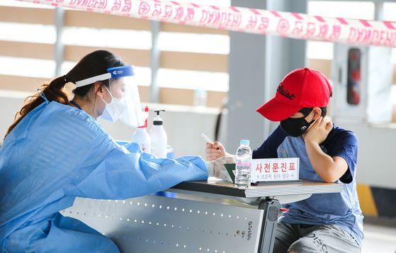 지난 8일 광주광역시 북구보건소를 찾은 초등학생이 코로나19 진단검사를 받기 전 사전 문진표를 작성하고 있다. 프리랜서 장정필