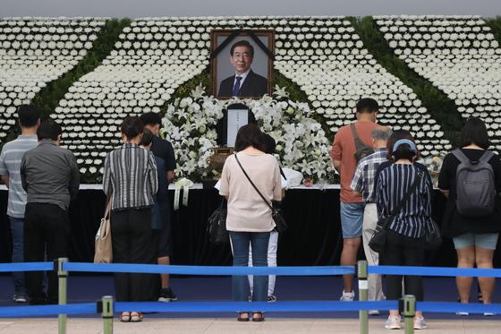 12일 서울광장에 마련된 고 박원순 서울시장 분향소를 찾은 시민들이 묵념하고 있다. 연합뉴스