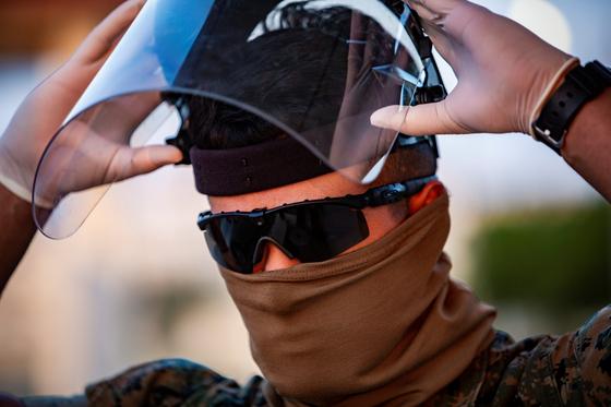 지난 4월 10일 일본 오키나와 주둔 미 해병대원이 코로나19 감염을 방지하기 위해 개인 방호장비를 착용하고 있다. [로이터=연합뉴스]