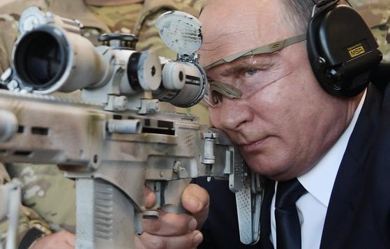 블라디미르 푸틴 러시아 대통령이 모스크바 인근 추빈카에 있는 군사시설인 애국자 공원을 방문해 저격 소통을 들고 목표물을 조준하고 있다. 애국주의를 내세운 푸틴이 정치적으로 저격하는 대상이 무엇인지에 관심이 몰리고 있다. 2018년 9월 자료 사진이다. AFP=연합뉴스