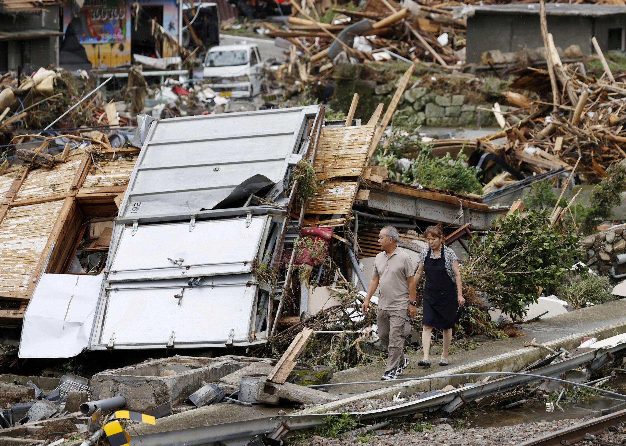 일본 규슈의 구마모토현 구마에서 6일 한 부부가 폭우에 무너진 부모의 집을 살펴보고 있다. 로이터=연합뉴스