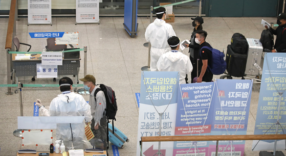 인천국제공항 1터미널에서 관계자들이 해외 입국자들을 안내하고 있다.  연합뉴스