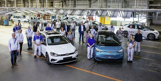 지난달 26일 독일 츠비카우의 폴크스바겐 공장에서 마지막 내연기관 차량인 골프 바리안트(왼쪽)를 생산한 뒤, 앞으로 생산하게 될 전기차 ID.3와 함께 직원들이 기념촬영하고 있다. [사진 폴크스바겐]