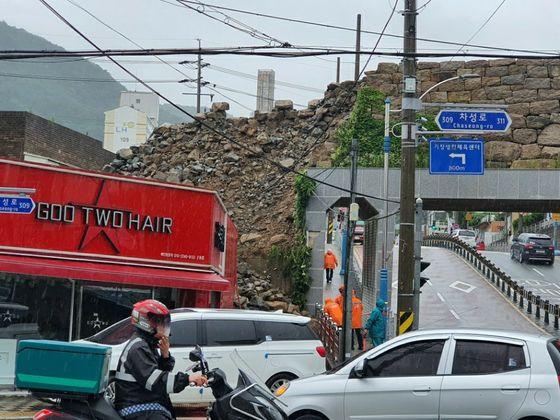 13일 낮 12시 30분쯤 기장군 읍내로의 굴다리 위에 축조한 성곽형태의 담장이 파손됐다. 경찰은 주변 교통을 통제하고, 기장군은 복구작업을 벌이고 있다. [사진 부산지방경찰청]