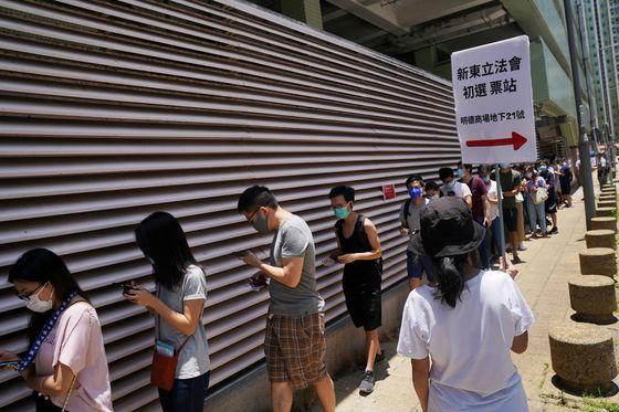 홍콩 범민주 진영이 지난 12일 실시한 입법회 예비선거의 투표장 앞에 신종 코로나바이러스 감염증(코로나19) 예방 마스크를 쓴 유권자들이 길게 줄지어 서 있다. 로이터=연합뉴스