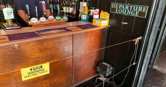 영국 콘월주의 한 술집 판매대 앞에 안내 문구와 함께 전기 펜스가 설치돼 있다. 술에 취한 손님들도 사회적 거리를 지키도록 술집 사장이 고안해 낸 아이디어다. [트위터 캡처]