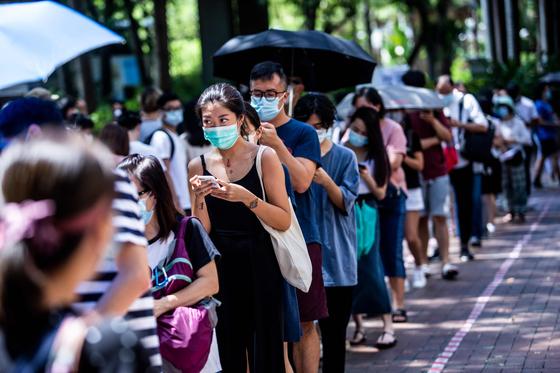 지난 12일(현지시간) 홍콩 민주진영 입법회의원 예비선거에 참여하기 위해 홍콩 시민들이 길게 줄을 서 있다. AFP=연합뉴스