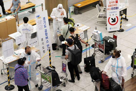 중앙재난안전대책본부가 13일부터 감염 위험도가 높은 방역강화 대상국가 외국인 입국자 전원은 출발일 기준 48시간 이전 PCR(유전자 증폭) 검사 음성 확인서를 의무적으로 제출해야 한다고 밝힌 가운데 12일 인천국제공항 제1터미널 입국장에서 외국인들이 해외입국자 교통수단 안내를 받고 있다. [뉴시스]