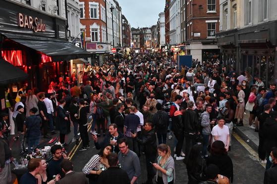 7월 4일 영국 런던 시내 거리가 사람들로 가득 찼다. 코로나19로 문을 닫았던 술집과 식당들이 3개월 만에 다시 문을 열자 인파가 몰렸지만 마스크를 쓴 사람은 보이지 않았다. [AFP=연합뉴스]