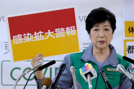 지난 15일 고이케 유리코 도쿄도지사가 기자회견에서 '감염 확대 경보'라고 적힌 판넬을 들고 있다. [AFP=연합뉴스]