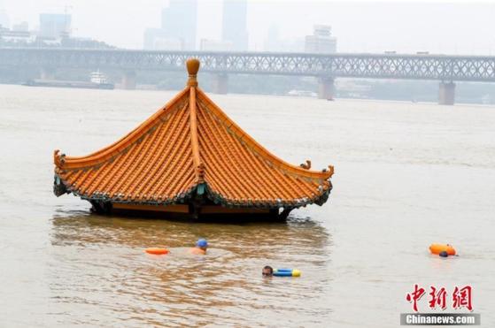 10일 후베이성 우한시 시민들이 홍수로 불어난 양쯔강에서 헤엄치고 있다. [중신망 캡처]
