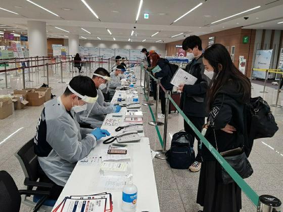 인천공항에 파견된 군인들이 입국자의 검역 서류를 확인하고 자가격리 앱을 설치해주고 있다. 인천공항에는 320명의 군인이 파견돼 검역 업무의 절반 가량을 도맡고 있다. 지금까지 8630명의 군인이 공항 검역을 도왔다. [사진 국방부]