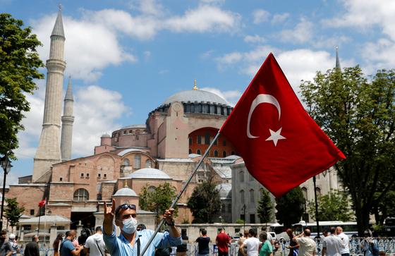 터키 최대 도시 이스탄불의 아야 소피아 앞에서 한 남자가 터키 국기를 들고 터키 민족주의를 상징하는 회색 늑대 를 손가락으로 나타내고 있다. 아야 소피아의 모스크화는 터키 민족주의와 포퓰리즘, 그리고 이슬람주의가 결합한 형태로 볼 수 있다. 로이터=연합뉴스