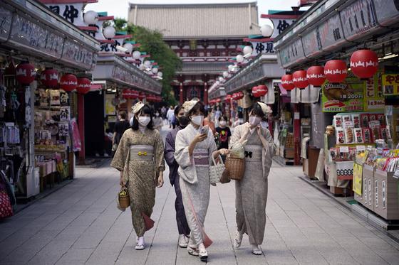 지난달 24일 일본 도쿄의 대표적인 관광지 아사쿠사에서 기모노를 입은 관광객들이 마스크를 쓰고 거리를 걷고 있다. [EPA=연합뉴스]