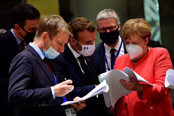 EU 회원국 정상이 20일(현지시간) 7500억 유로 기금 조성을 위한 회의 중 서류를 검토하고 있다. 오른쪽에서 세번째 프랑스 마크로 대통령과 맨 오른쪽의 메르켈 총리가 결정적 역할을 해냈다. AFP=연합뉴스