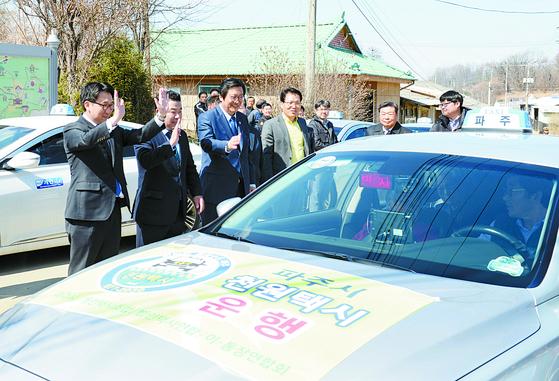 최종환 파주시장(왼쪽) 등이 지난해 4월 1일 '천원택시' 첫 이용객에게 손을 흔들며 마중하고 있다. [파주시]