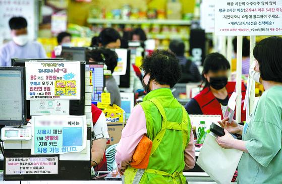 (신종 코로나바이러스감염증(코로나19) 영향으로 위축됐던 소비자심리가 긴급재난지원금 등으로 넉 달 만에 풀린 것으로 보인다. 한국은행이 발표한 5월 소비자심리지수(CCSI)는 77.6으로 전월 대비 6.8포인트 상승하며 4개월 만에 반등했다. 이달 소비자 동향 조사는 지난 11~18일 전국 2500가구를 대상으로 실시됐다. 26일 서울 중구 약수시장의 한 소규모 마트에서 시민들이 계산을 위해 줄 서 있다.뉴스1