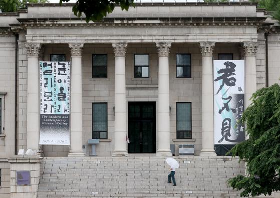 코로나19로 두 달 가까이 휴관했던 국립현대미술관 덕수궁관 '미술관에 書: 한국 근현대 서예전'이 22일 재개관해 관람객을 맞고 있다 23일 우산을 들고 전시장을 찾은 한 관람객의 모습 . 최정동 기자