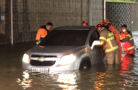 23일 인천 중구 운북동의 한 도로에서 차량 하부가 집중호우로 인해 물에 잠겨 소방대원들이 구조작업을 벌이고 있다. 인천에는 23일 하루동안 200㎜가 넘는 비가 내렸다. 사진 인천소방본부