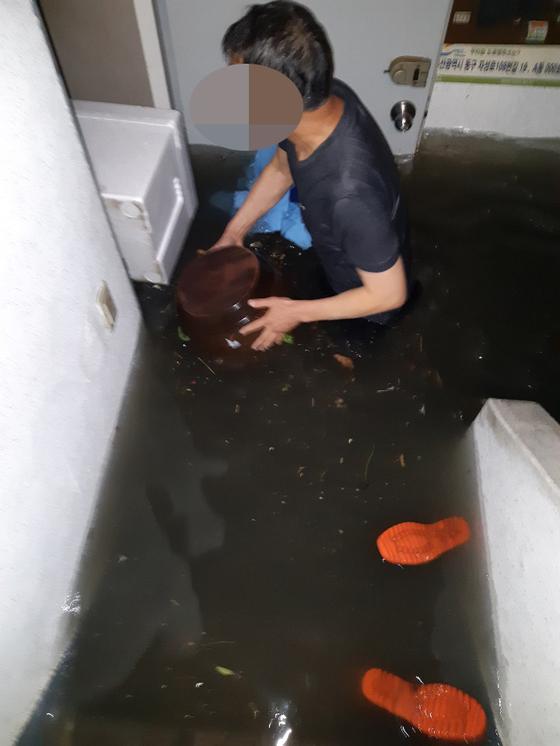 집중호우가 내린 23일 오후 부산 동구 동천이 범람하면서 인근의 한 아파트 1층이 침수됐다. 일부 주민은 대피소로 이동 중이다. 독자 제공. 연합뉴스