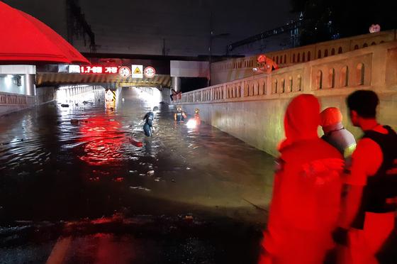 23일 많은 비가 내린 부산 동구 초량동 부산역 인근 제1지하차도에 출동한 소방대원들이 구조작업을 벌이고 있다. 사진 부산소방재난본부