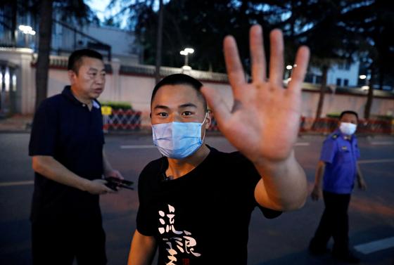 중국 사복 경찰이 쓰촨성 청두의 미국 영사관 앞에서 취재진에게 다가와 카메라를 제지하는 손짓을 하고 있다고 로이터통신이 전했다.[로이터=연합뉴스]