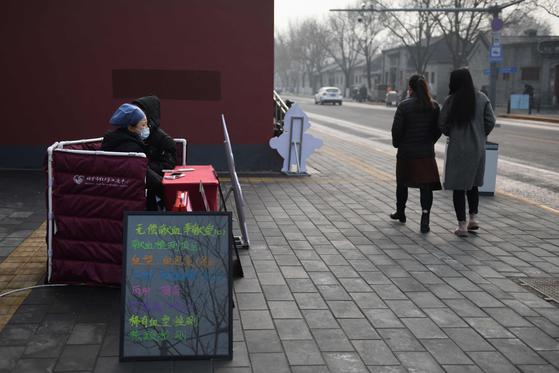 지난 2월 13일 마스크를 쓴 중국 베이징 적십자센터 직원들이 이동식 헌혈대를 세우고 헌혈자를 기다리고 있다. 코로나19 사태로 중국에서 헌혈이 급격히 줄면서 매혈이 성행하고 있다. [AFP=연합뉴스]