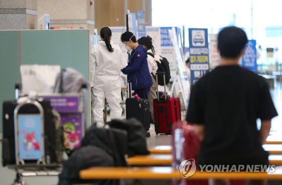 지난달 23일 오후 인천국제공항에서 관계자들이 해외 입국자들을 안내하고 있다. 연합뉴스