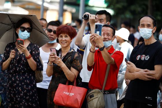 27일(현지시간) 중국인들이 중국 청두 주재 미국 영사관 앞에 모여 휴대전화와 카메라로 영사관 폐쇄 장면을 찍고 있다. [로이터=연합뉴스]