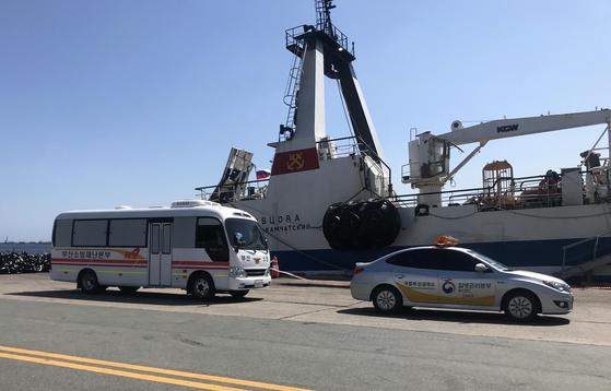 지난 17일 부산 감천항에서 부산소방재난본부가 러시아 선박에 탑승해 있던 코로나19 확진자를 차량으로 이송하고 있다. 부산소방재난본부