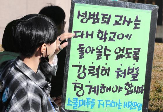 2018년 11월3일 오후 서울 파이낸스 빌딩 앞에서 열린 '여학생을 위한 학교는 없다' 학생회 날 스쿨미투 집회에서 참가자들이 성범죄 교사 처벌에 대한 문구를 보고 있다.   연합뉴스