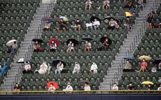 28일 서울 잠실야구장에서 열린 2020 KBO리그 프로야구 키움 히어로즈와 두산 베어스의 경기. 관중들이 우산을 쓰거나 우비를 입은 채로 경기를 지켜보고 있다. 연합뉴스