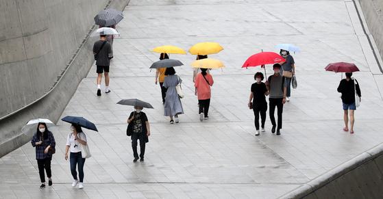 전국에 장맛비가 내린 27일 오후 서울 중구 동대문역사문화공원역 앞에서 우산을 쓴 시민들이 발걸음을 재촉하고 있다.  기상청은 이날 장마전선이 북상하면서 남부지방을 중심으로 많은 비를 뿌린다고 전망했다. 뉴스1