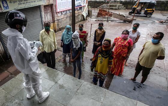 인도 뭄바이의 빈민가에서 헬멧을 착용한 보건 담당 직원이 주민들을 대상으로 발열 검사를 하고 있다. [EPA=연합뉴스]