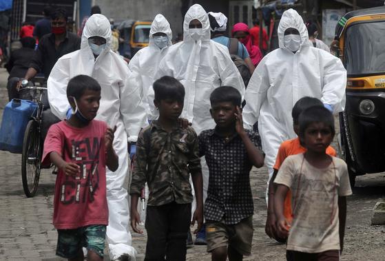 방호복을 입은 의료진이 코로나19 진단 검사를 위해 인도 뭄바이 빈민가에 도착했다. [AP=연합뉴스]
