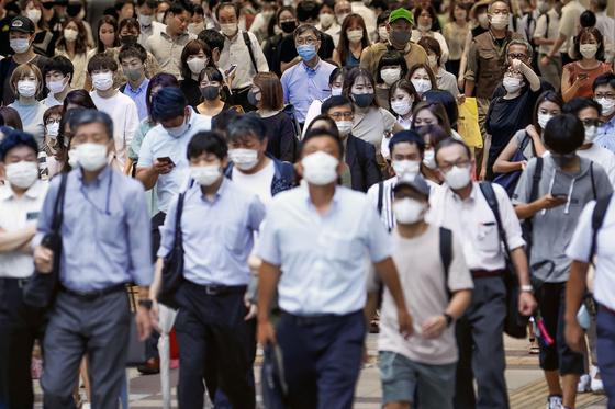 지난 29일 마스크를 착용한 사람들이 일본 오사카 시내를 지나고 있다. [AP=연합뉴스]