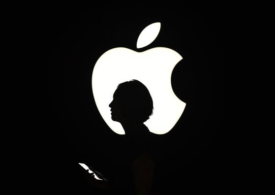 애플 로고 앞을 한 시민이 지나고 있다. 애플은 30일(현지시간) 어닝 서프라이즈와 함께 주가 액면분할을 발표했다. AFP=연합뉴스