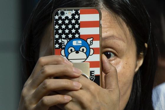 한 여성이 지난달 26일 중국 청두에서 성조기가 그려진 휴대폰으로 미국 총영사관을 찍고 있다. 중국 정부의 폐쇄 명령으로 청두 주재 미국 총영사관은 지난 27일 문을 닫았다. [AP=연합뉴스]