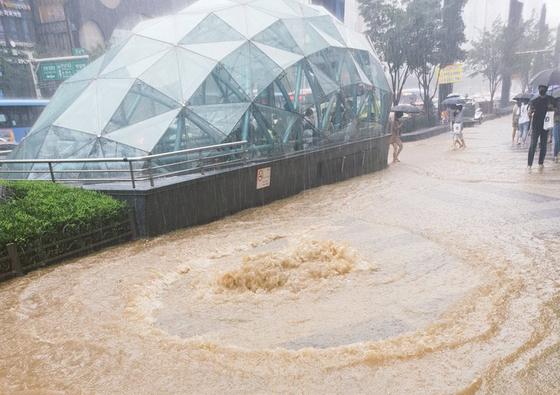 서울 전역에 호우 특보가 내려진 1일 서울 강남역 인근 맨홀 뚜껑에서 하수가 역류해 인근 인도가 흙탕물로 뒤덮여 있다. 연합뉴스