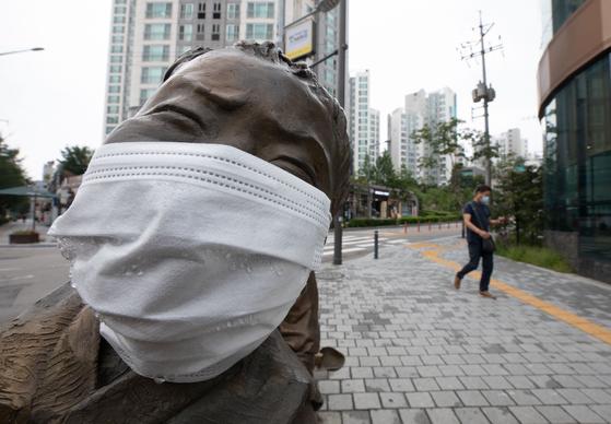 지난달 19일 오후 서울 마포구의 한 거리에 위치한 동상에 마스크가 씌어져 있다. 방역당국은 마스크를 쓰지 않는 경우, 마스크를 쓰는 경우보다 감염의 가능성이 5배가 높은 것으로 나타났다고 밝혔다. 뉴스1