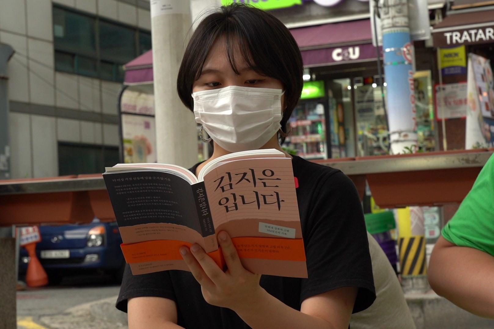 지난달 26일 서울 동대문구 외대앞역 광장에서 '김지은입니다' 독서회 참가자가 책을 읽고 있다. 백경민 인턴