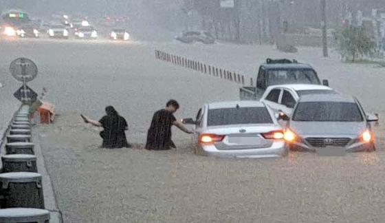 충남 천안에 3일 폭우가 쏟아진 가운데 시민들이 물에 빠진 차를 두고 급히 빠져나오고 있다. 연합뉴스
