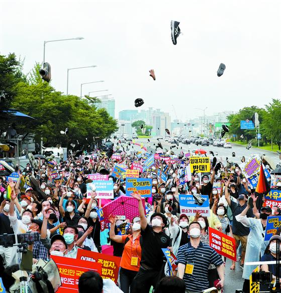 정부의 부동산 규제 정책에 반대하는 시민모임 회원들이 지난 1일 서울 여의도에서 집회를 열고 신발을 던지는 퍼포먼스를 하고 있다. 임현동 기자