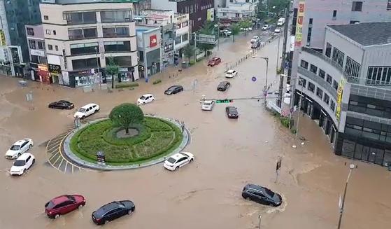 폭우가 쏟아진 3일 충남 아산시 온양관광호텔 앞 로터리가 침수돼 차량이 물길을 헤치며 가고 있다. 연합뉴스