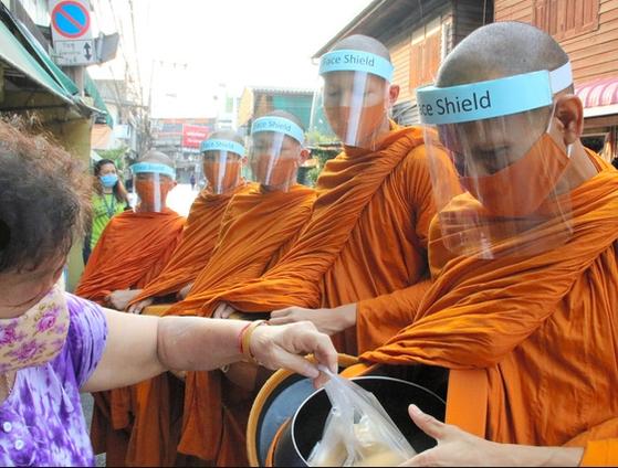 태국의 스님들이 탁발을 하고 있다. 코로나 사태로 인해 마스크와 얼굴 가림막을 한 채 마을을 돌고 있다. [중앙포토]