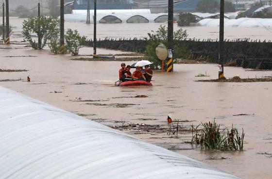 3일 오후 충남 천안시 수신면 장신리 한 도로가 침수돼 소방대원들이 고무보트로 마을 주민 등을 구출하고 있다. 이날 폭우로 병천천 둑 일부가 무너지며 하천물이 마을로 통하는 길을 막았다. 연합뉴스
