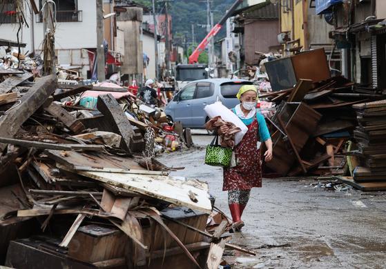 지난달 11일 구마모토현 히토요시 지역에서 한 주민이 폭우로 무너진 건물 잔해가 쌓인 거리를 지나고 있다. [AFP=연합뉴스]