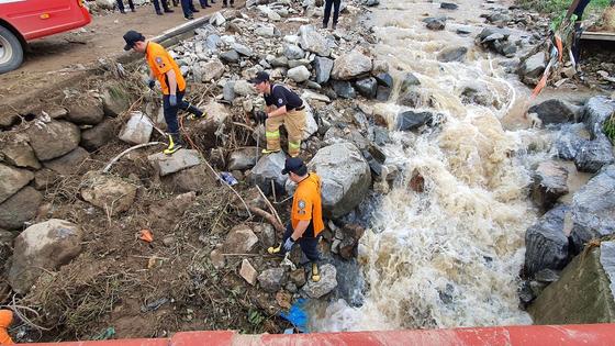 지난 4일 충남 아산시 송악면 유곡3리 하천에서 119구조대와 경찰이 폭우에 휩쓸려 실종된 마을주민 2명을 수색하고 있다. 신진호 기자